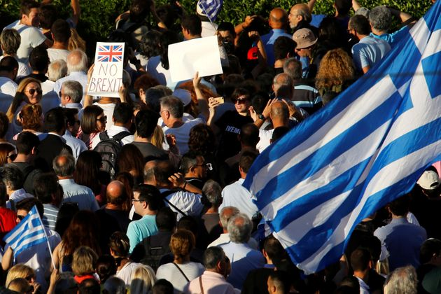 An anti-government demonstrator waves a Greek flag next to a placard that reads