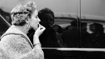 7th November 1953:  A contestant in a 'Miss World' beauty competition sponsored by Mecca Dancing applying her lipstick using a shiny car as a mirror. Original Publication: Picture Post - 6785 - The Beauty Contest Business - pub. 1953 (Photo by Thurston Hopkins/Picture Post/Getty Images)