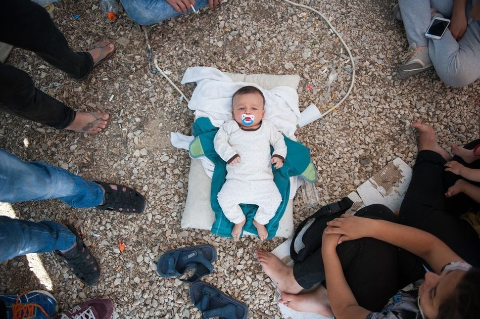"A Syrian baby lays on the ground in Kara Tepe camp, Lesbos. The baby's family cannot even afford milk. ""I am here"