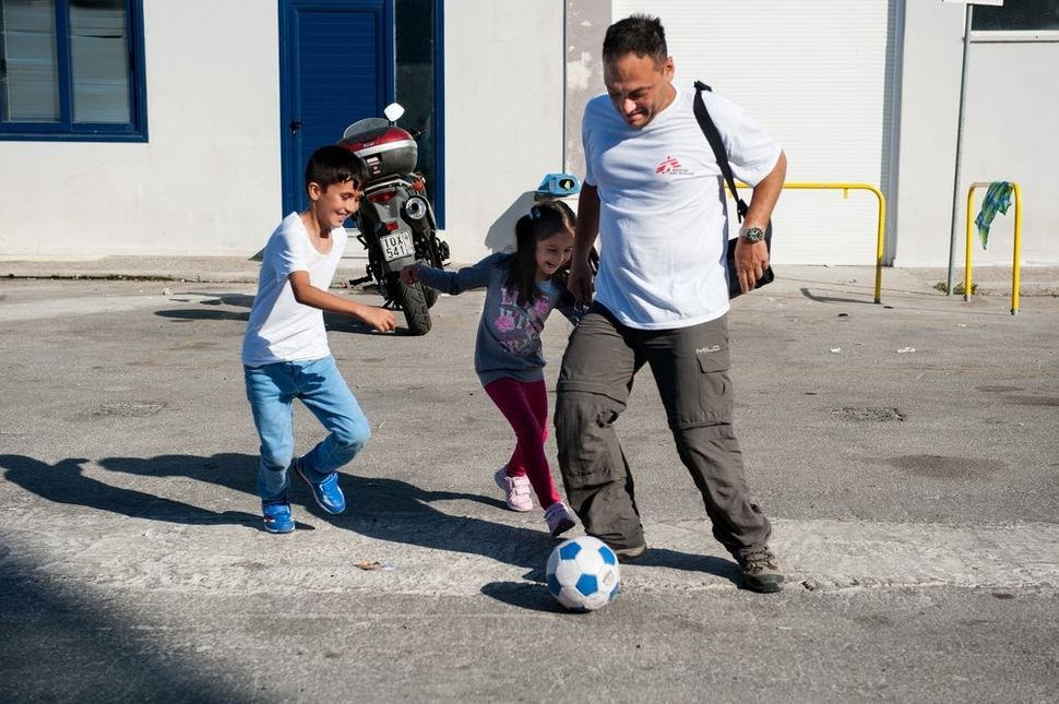 Doctors Without Borders surgeon Dimitris Giannousis plays football with children refugees at the Greek port of Lesbos. &ldquo