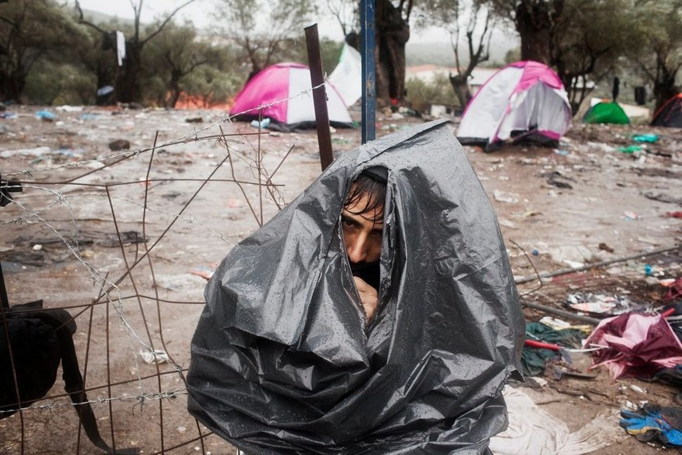 An Afghan refugee wears a plastic garbage bag to protect himself from the storm at Moria camp in Lesbos, as he waits for his