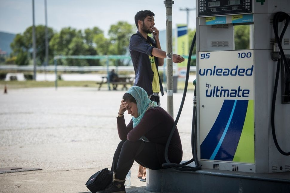 A woman cries in a gas station near Idomeni camp during the evacuation operation.