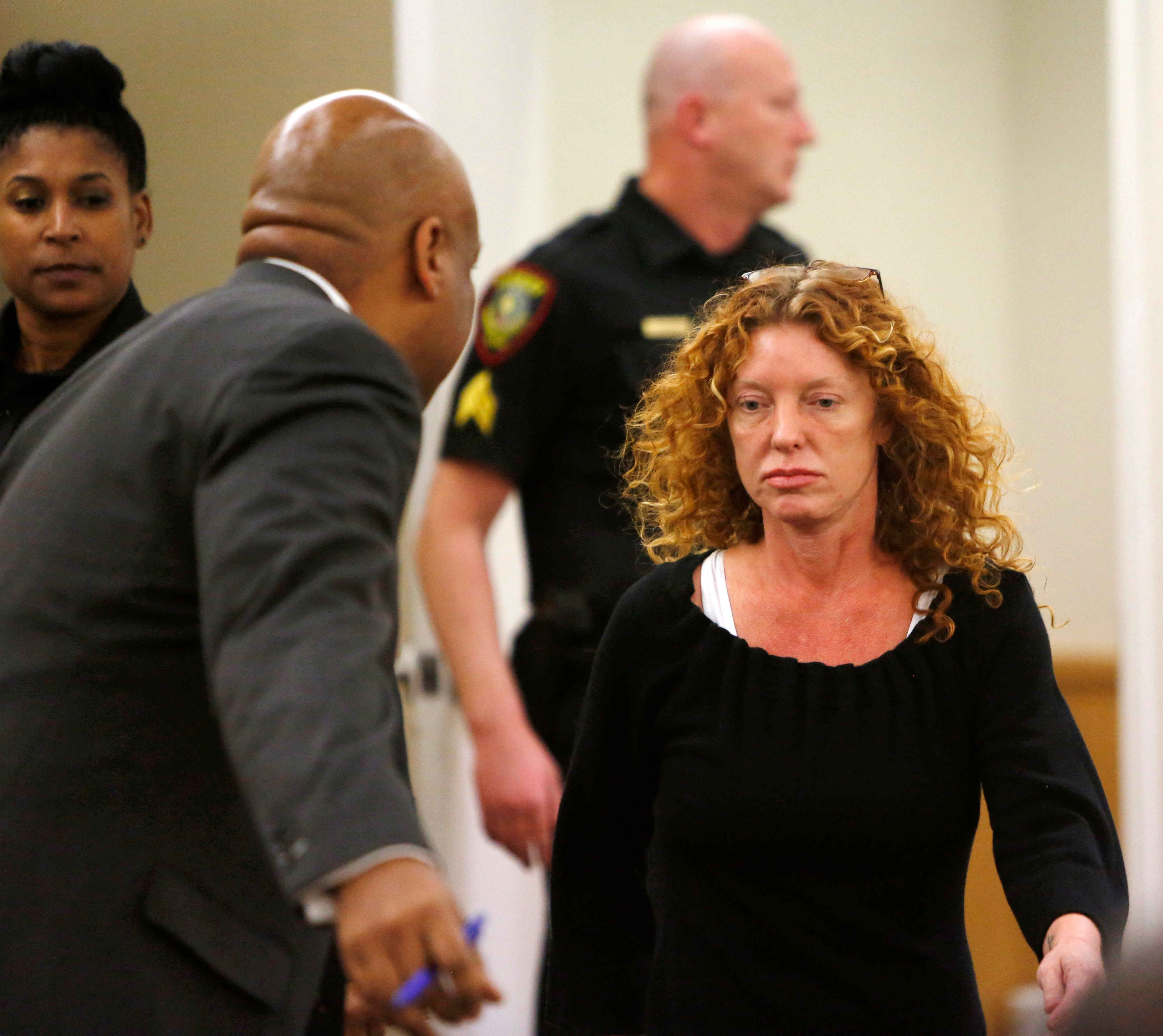 Tonya Couch (R) is escorted to her defense team in  Criminal District Court in Fort Worth, Texas, January 11, 2016.  A Texas judge on Monday slashed the bond required for a mother charged with helping her teenage son flee to Mexico after was suspected of violating a probation deal that kept him out of prison following a fatal drunk driving crash.  REUTERS/David Kent/Ft. Worth Star-Telegram/Pool