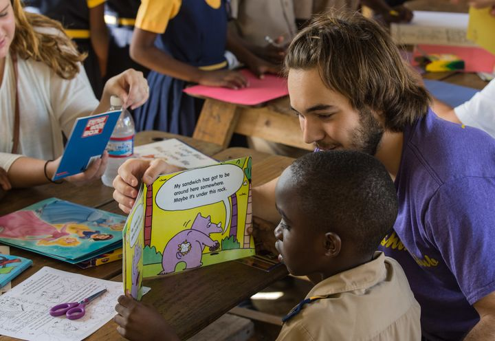 <p>Millennial Jordan Kalkhurst reading with students in a school in Ocho Rios, Jamaica</p>