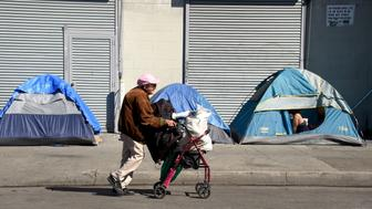 A woman pushes her walker past tents housing the homeless in Los Angeles, California on February 9, 2016. Los Angeles City and County officials are voting February 9 on plans aimed at ending homelessness in the community, mostly by making permanent housing available to the tens of thousands of people who are homeless.  / AFP /  AND Frederic J. BROWN        (Photo credit should read FREDERIC J. BROWN/AFP/Getty Images)