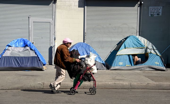 A woman pushes her walker past tents housing the homeless in Los Angeles, California.