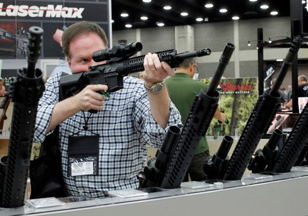 James Bell from Nashville, TN, look over rifle scopes from Burris Riflescope at the National Rifle Association's...