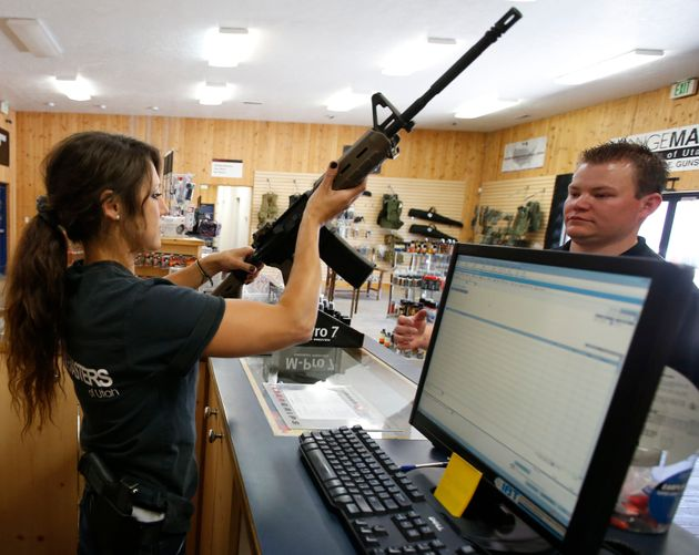 Courtney Manwaring, (L) shows an AR-15 semi-automatic gun to David Barker (R) at Action Target on June...