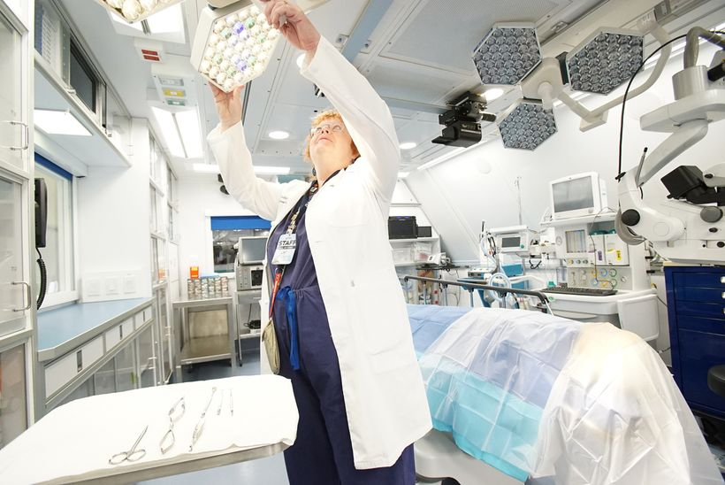Dr. Rosalind Stevens adjusts the lights in the Operating Room of the Flying Eye Hospital.