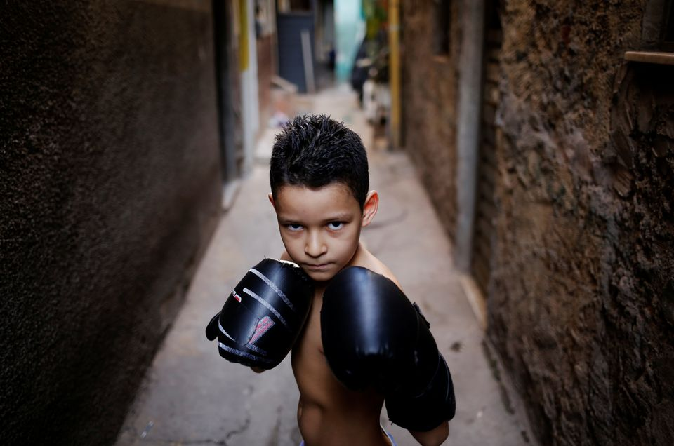 """Juan, 7, poses for a photograph in an alley, also known as """"viela"""", in the Mare favela of Rio de Janeiro, Brazil, June 2, 201"""