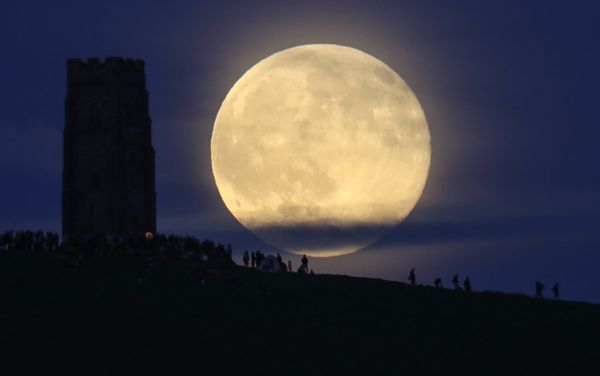 A full moon rises behind Glastonbury Tor as people gather to celebrate the summer solstice on June 20, 2016 in Somerset, Engl