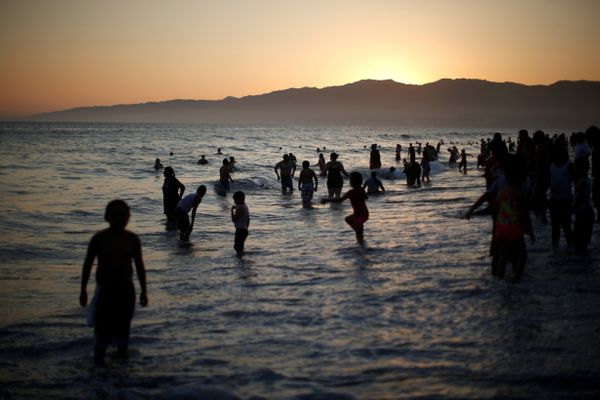 People cool off in the Pacific Ocean during a record-setting heat wave across the U.S. Southwest, on the summer solstice in S