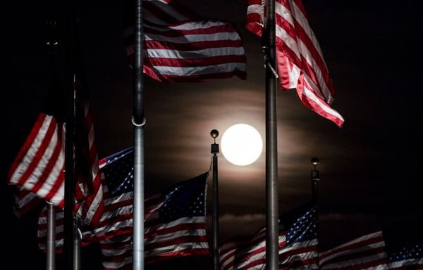 The full moon rises above the flags at the Washington Monument in Washington on Monday, June 20, 2016.