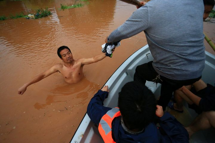 Rescuers save a man wading in flood water after heavy rainfall in Hengyang, Hunan Province, China, on June 15, 2016.