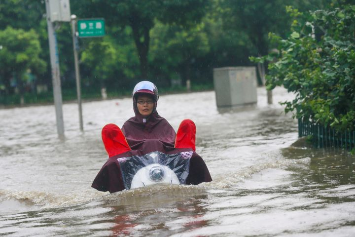A resident rides a vehicle along a flooded street in Liuzhou, Guangxi Zhuang Autonomous Region, China, on June 14, 2016.
