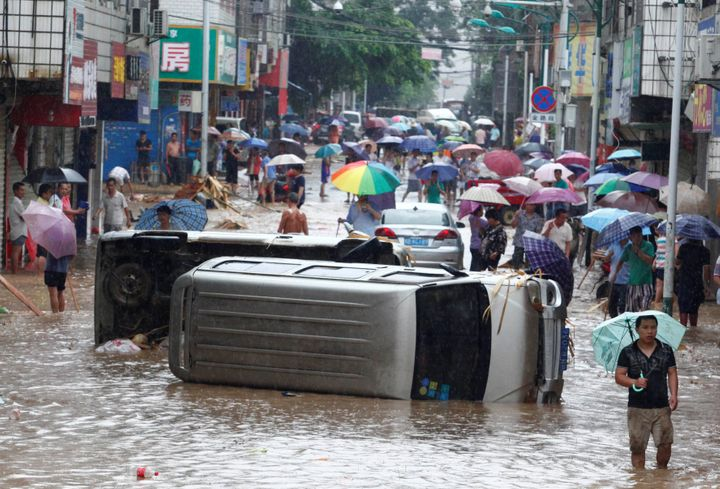 Automobiles are seen overturned on a flooded street in Liuzhou, Guangxi Zhuang Autonomous Region, China, on June 14, 2016.