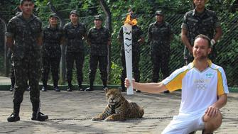 Brazilian physiotherapist Igor Simoes Andrade poses for picture next to jaguar Juma as he takes part in the Olympic Flame torch relay in Manaus, Brazil, June 20, 2016. Picture taken June 20, 2016.  REUTERS/Marcio Melo  FOR EDITORIAL USE ONLY. NO RESALES. NO ARCHIVES - RTX2HE53