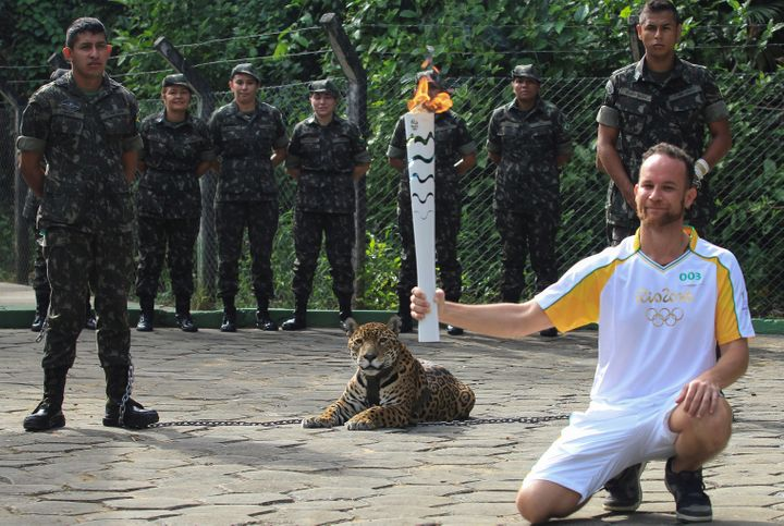 Brazilian physiotherapist Igor Simoes Andrade poses for picture next to jaguar Juma as he takes part in the Olympic Flame tor
