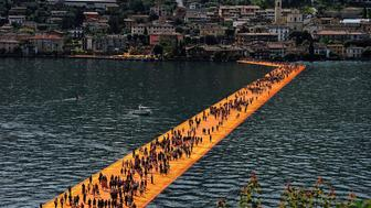 People walk on the installation 'The Floating Piers' on the Iseo Lake by the Bulgarian artist Christo Vladimirov Yavachev known as Christo on June 8, 2016 in Iseo, Italy.