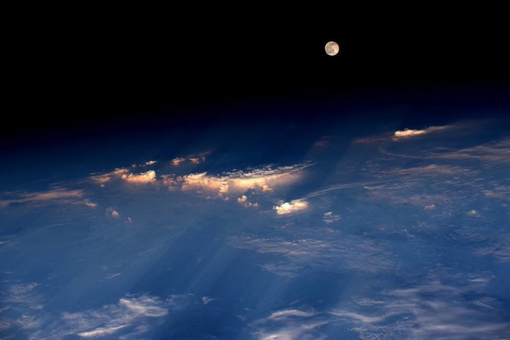 Astronaut Jeff Williams took this photograph of the rare Strawberry Moon emerging from the clouds while orbiting Earth from t