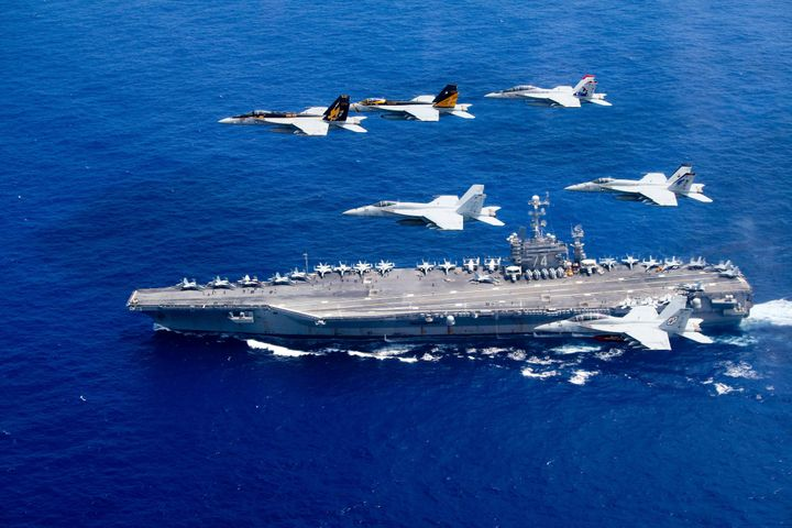 A combined formation of aircraft pass in formation above the Nimitz-class aircraft carrier USS John C. Stennis in the Philipp
