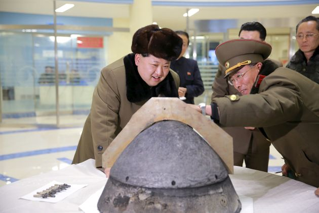 North Korean leader Kim Jong Un looks at a rocket warhead tip at an unidentified location in this undated...