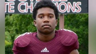 Zaevion Dobson poses for a picture in his high school football jersey