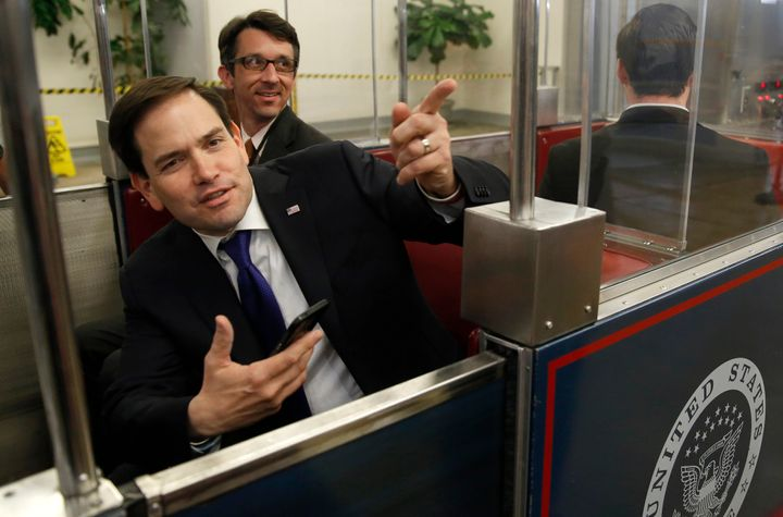 Former Republican presidential candidate Marco Rubio (left) talks to reporters while waiting for the Senate's subway to depar