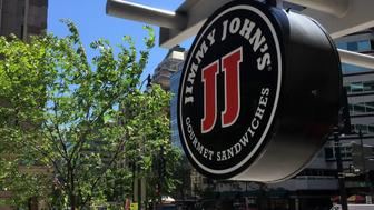 A logo of the sandwich restaurant chain, specializing in delivery Jimmy John's hangs outside one of their shops in downtown Washington, DC, June 9, 2016 A US sandwich chain is being sued for locking its low-paid workers into non-compete agreements more typical of high-tech workers or top executives. The state of Illinois, where Jimmy John's is headquartered, accuses the company of requiring employees to sign clauses barring them from working at competing sandwich stores within two miles of one of its outlets for at least two years after leaving the company.  / AFP / Mladen Antonov        (Photo credit should read MLADEN ANTONOV/AFP/Getty Images)