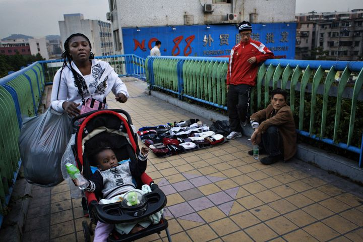FILE PHOTO: An African woman with a baby in a stroller passes a pedestrian bridge where Chinese street vendors are trying to