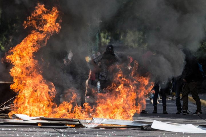 Masked protesters block a street in Mexico City on Monday in protest for the recent violent acts in Oaxaca state.