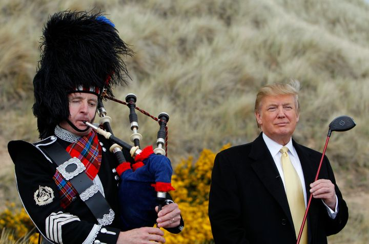 Donald Trump stands next to a bagpiper during a media event on the sand dunes of the Menie estate, the site for Trump's propo