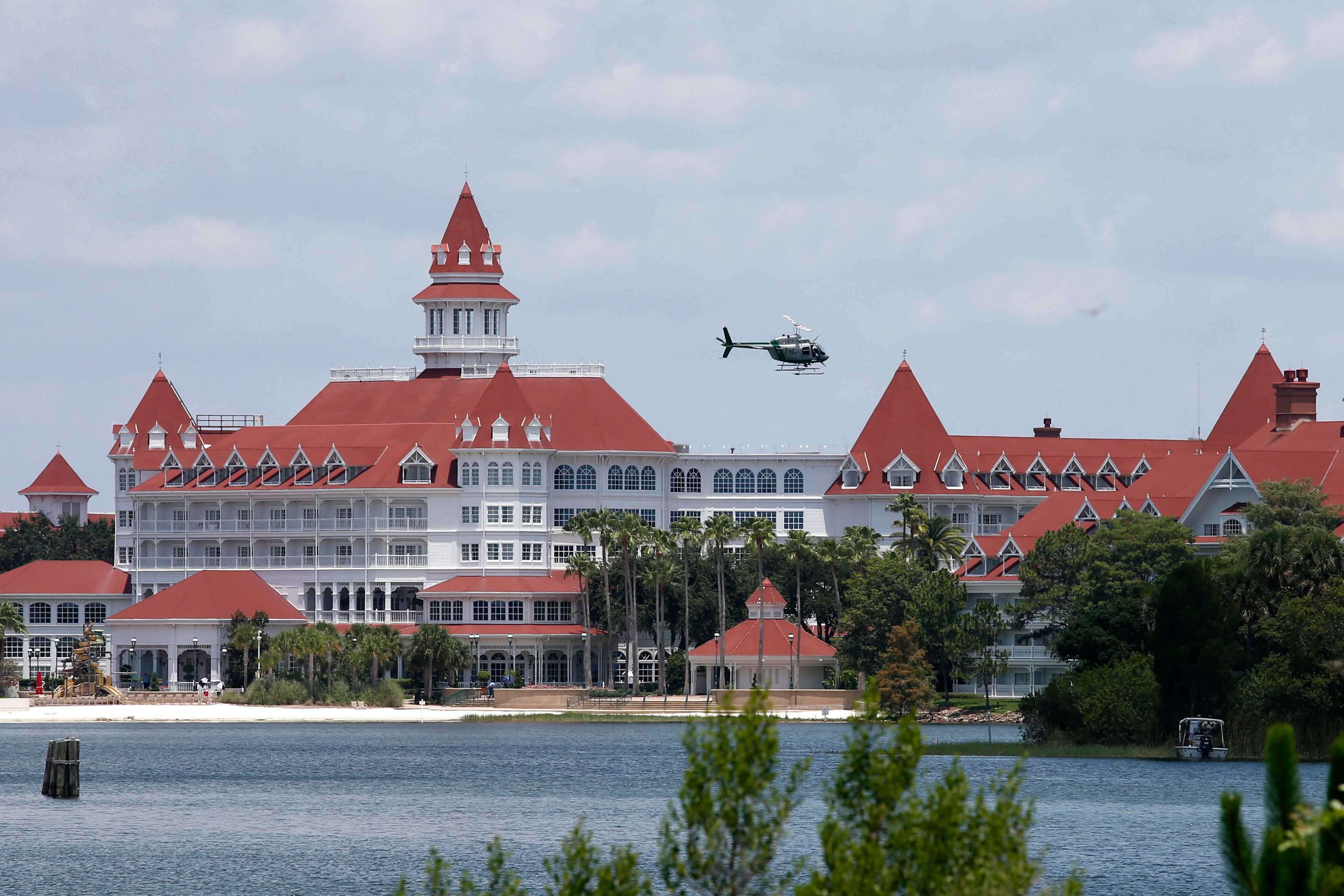 A Florida Fish and Wildlife Conservation Commission helicopter flies over the Seven Seas lagoon at Walt Disney World resort after an alligator dragged a two-year-old boy into the water in Orlando, Florida, U.S. June 15, 2016.   REUTERS/Adrees Latif