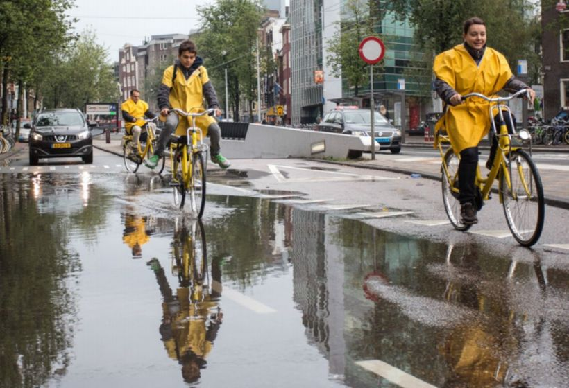 <i>Hardy Amsterdam cyclists navigate puddles in&nbsp;Nieuwezijdskolk, central Amsterdam.</i>