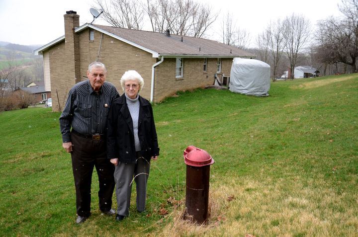 Jesse and Shirley Eakin stand by the water well they no longer use at their home in Avella, Pa. Delivered water is stored in