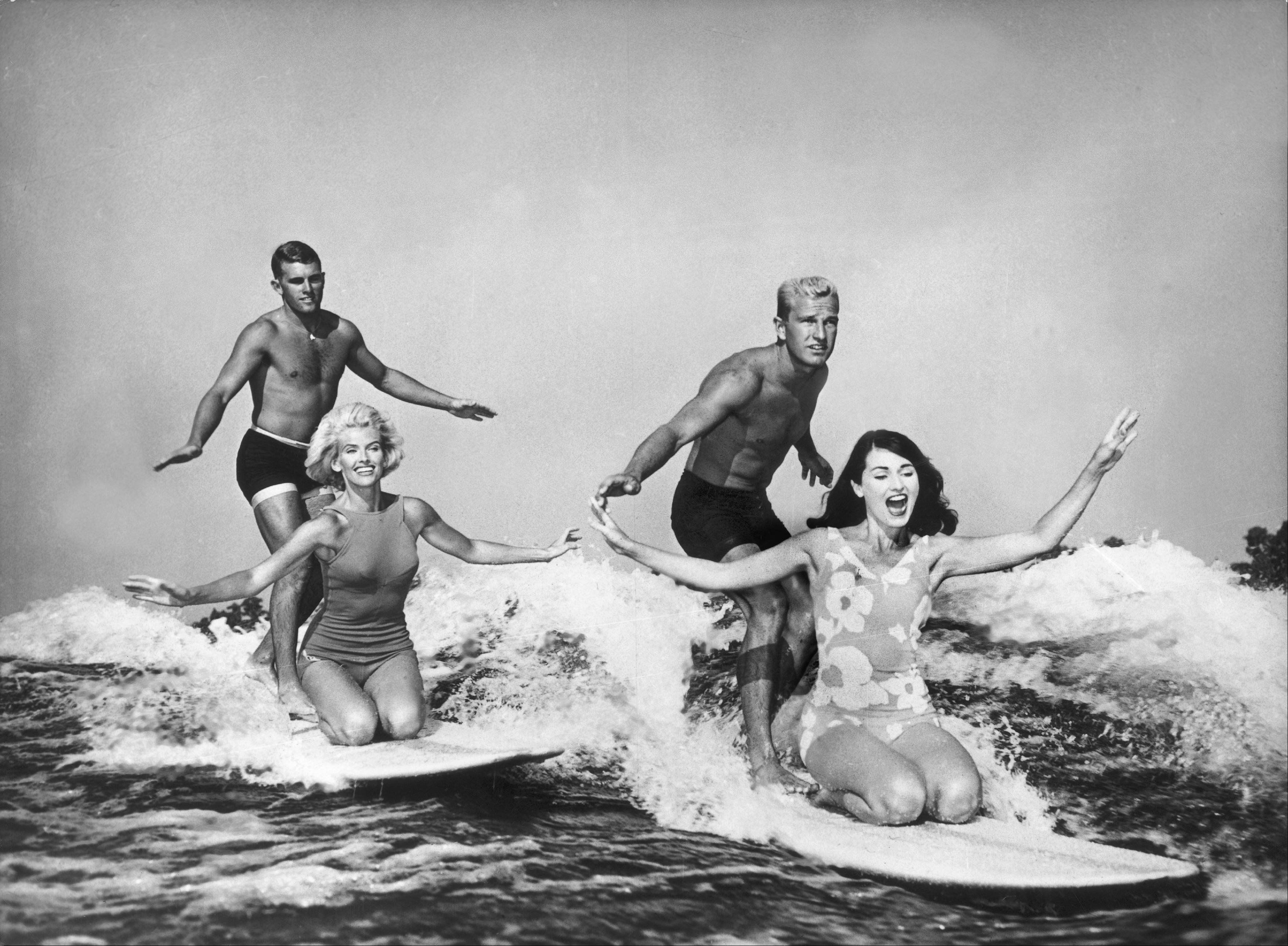 Water ski champions demonstrating their skills as they ride the wake of a boatwithout a tow-line in California.(1