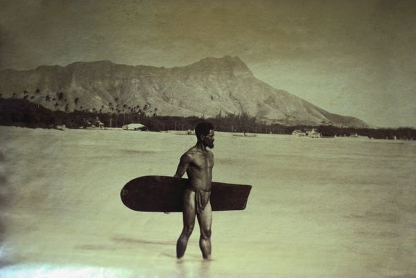 A Native Hawaiian with a traditional surfboard standing on a beach in Waikiki on the Hawaiian island of Oahu. (1890)