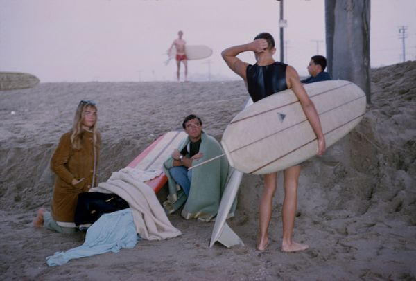 View of a group of surfers on the sand under the pier at Surfrider Beach, Malibu, California, January 1966. The photo was tak