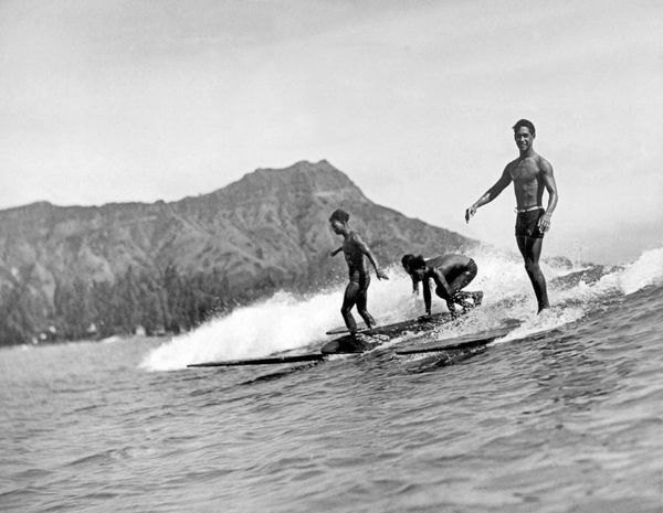 Three native surfers ride their boards with ease at Waikiki Beach, with Diamond Head in the background, Honolulu, Hawaii, 192