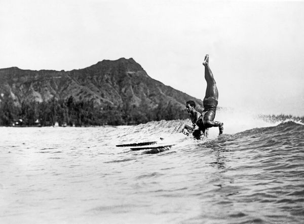 A surfer at Waikiki Beach stands on his head as he rides a wave into the shore, Honolulu, Hawaii, circa 1925. Diamond Head is