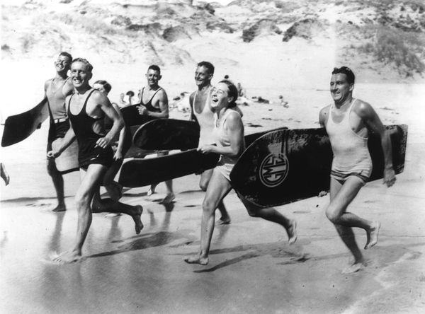 A group of surfers running on the beach at Sydney carrying their surfboards. (May 1931)