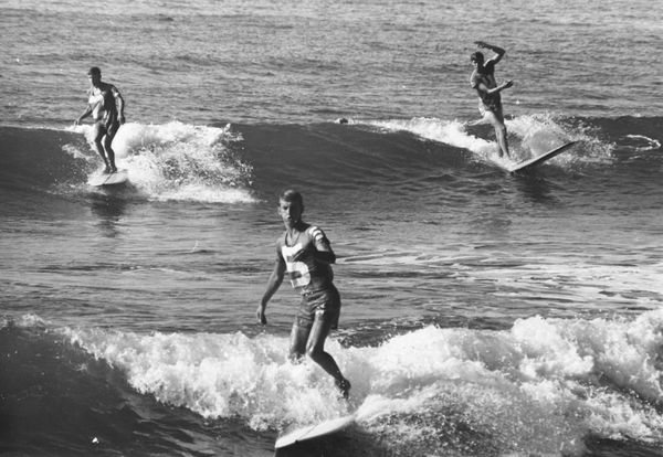 Surfers Jeff Hakman, Bob Conneeley and John Day ride the small waves on a Pacific beach. (1970)