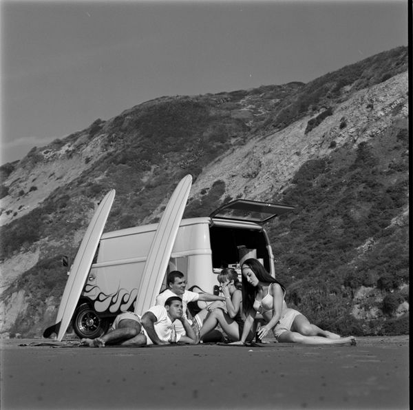 A group of youngsters enjoy a day at the beach reclining next to the US Rubber Custom VW Volkswagen Bus and their surf b