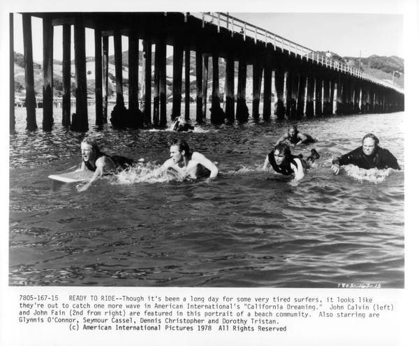 "John Calvin (left), John Fain (2nd from right) ride out with other surfers to catch a wave in a scene from the film ""Californ"