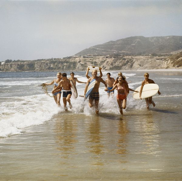 A group of surfers running along the shore.