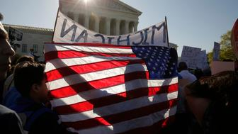 Immigration activists holding an American flag and a large Michigan sign rally outside the U.S. Supreme Court as justices hear arguments in a challenge by 26 states over the constitutionality of President Barack Obama's executive action to defer deportation of certain immigrant children and parents who are in the country illegally in Washington April 18, 2016.  REUTERS/Joshua Roberts  TPX IMAGES OF THE DAY