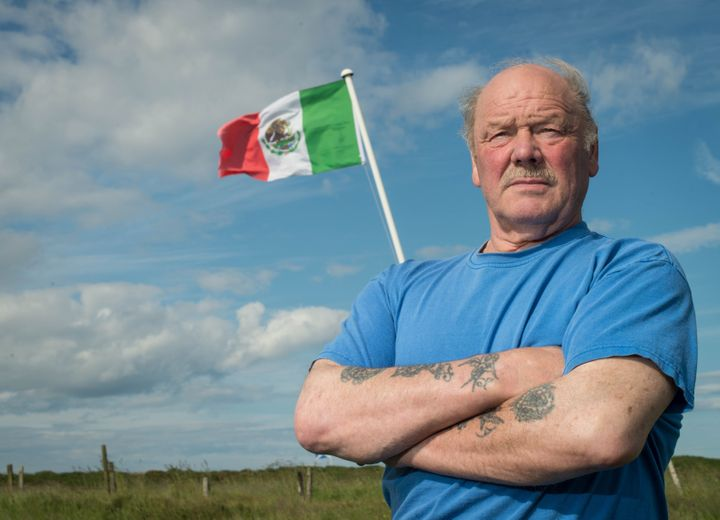 Michael Forbes poses for a photograph beside the Mexican flag he erected alongside Donald Trump's International Golf Links co