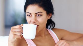 Closeup of attractive young woman drinking coffee at home