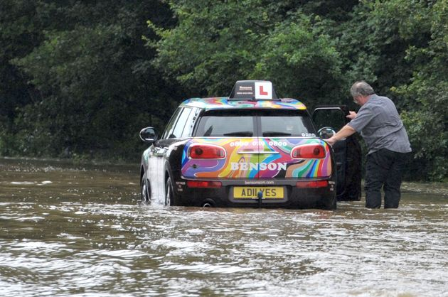 A driving instructor has to push his vehicle after he became stuck in the flooded road in Writtle,