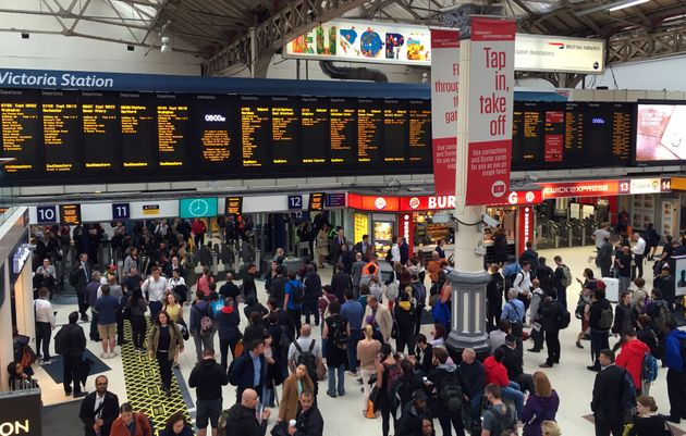 Commuters at Victoria Station as torrential downpours wreak havoc on the capital's transport